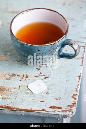 Cup of tea with teabag on blue textural background - Stock Photo