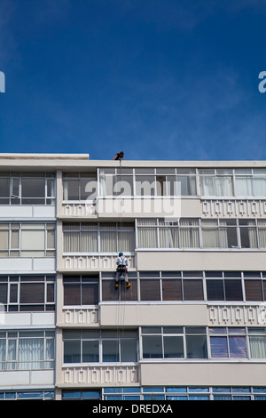 Window Cleaner Abseiling on Apartment exterior in sea Point - Cape Town - South Africa - Stock Photo