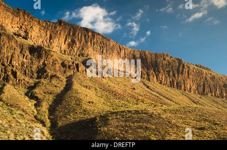 Thick sequence of trachyte and phonolite lava flows forming the east wall of Barranco de Fataga, Arteara, Gran Canaria - Stock Photo