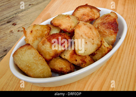 Crispy Roast potatoes in a serving dish against a traditional rustic kitchen table - Stock Photo