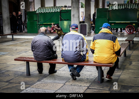 Three men watching a street entertainer in the North Hall in Covent Garden. - Stock Photo