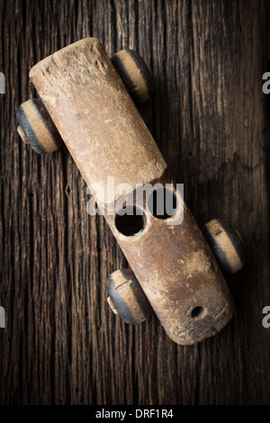 An old wooden toy car weathered from years of play on a rustic old floor. - Stock Photo