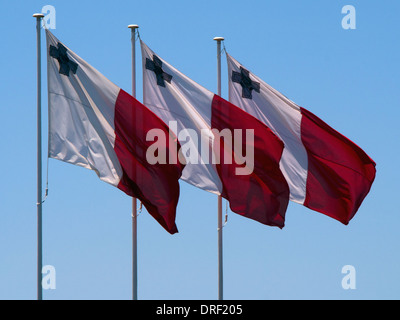 A trio of Maltese flags flutters proudly in the Valletta breeze  the George Cross a reminder of national bravery - Stock Photo