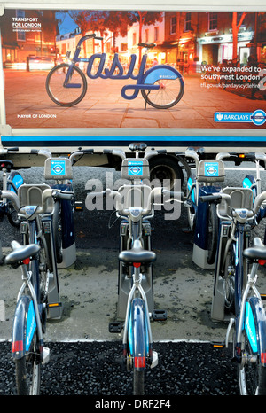 London, England, UK. Boris Bikes / Cycles for Hire, in front of a Transport for London van with advertising poster - Stock Photo