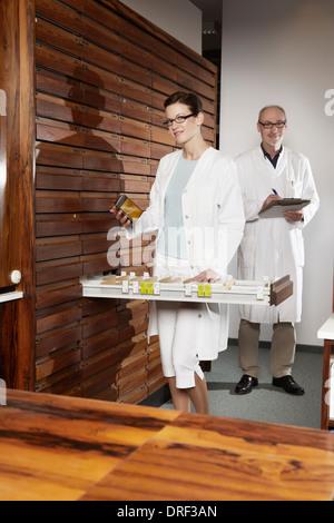 Pharmacists Working In Drugstore, Munich, Bavaria, Germany - Stock Photo