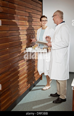 Pharmacists Working In Drugstore, Munich, Bavaria, Germany - Stock Photo