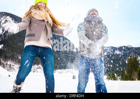 Couple Having Snowball Fight, Spitzingsee, Bavaria, Germany - Stock Photo