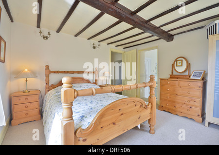 Spare bedroom with pine framed double bed and pine furniture - Stock Photo