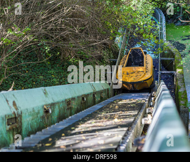 Old yellow boat, rails and murky, slimy pond at the abandoned, derelict, disused amusement park - Spreepark, Planterwald, - Stock Photo