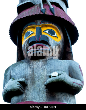 A figure on a native totem pole is hand carved out of red cedar. - Stock Photo