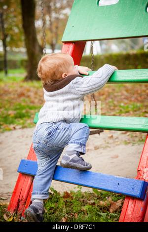 Toddler climbing on jungle gym, Osijek, Croatia - Stock Photo