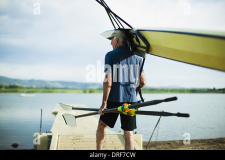 Colorado USA middle-aged man carrying oars and rowing shell - Stock Photo