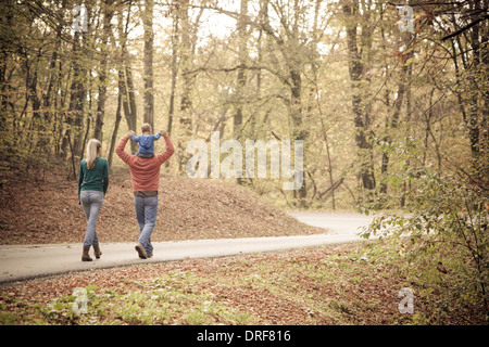 Parents with son walking across road, Osijek, Croatia - Stock Photo