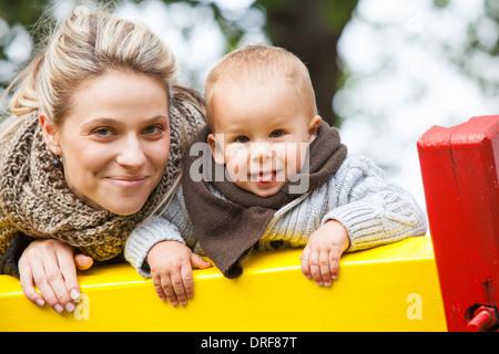 Mother and son on a jungle gym, portrait, Osijek, Croatia - Stock Photo