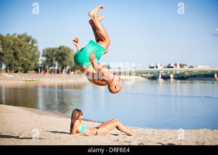 Young man somersaulting on the beach, Drava river, Osijek, Croatia - Stock Photo