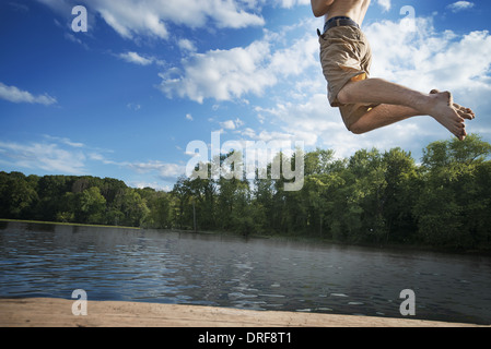 New York state USA boy running jumping into water from wooden jetty - Stock Photo