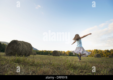 New York state USA field hay bales girl dancing arms outstretched - Stock Photo