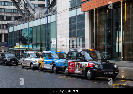 Colourful Taxis parked in St Mary's Gate_Hackney Cabs, Private Hire Vehicles in Manchester City Centre, Lancashire, - Stock Photo