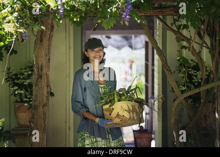 New York state USA young woman in farmhouse kitchen with large window - Stock Photo