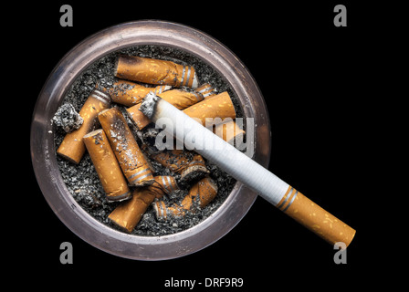 A grungy ashtray full of ash and cigarette butts with one lit cigarette on a black background and room for copy. - Stock Photo