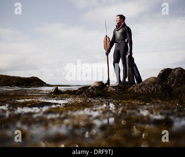 USA man in wetsuit standing on shore with large spear - Stock Photo