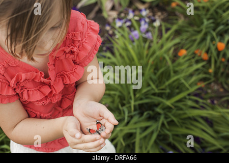 Utah USA young girl looking at colourful butterfly - Stock Photo