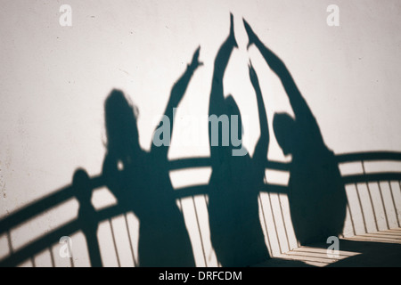 Creative photo of happy people shadows on white wall gesturing high five - Stock Photo