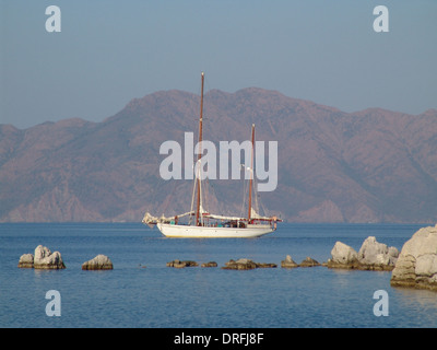 old two-master schooner is sailing in calm waters. in the background the turkish coast - Stock Photo