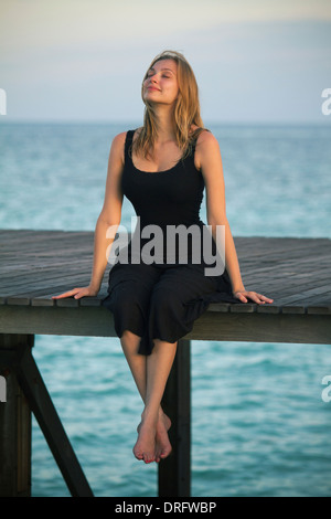 Young woman in sundress relaxes on a boardwalk, Lankayan Island, Borneo, Malaysia - Stock Photo