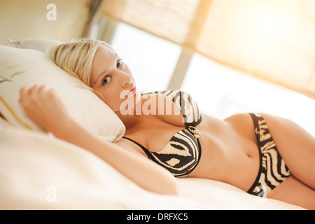Young woman in bikini relaxes on a bed, looking at camera, Dubrovnik, Croatia - Stock Photo