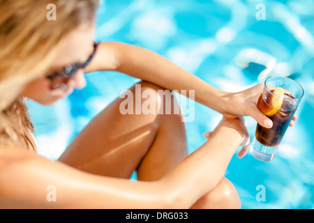 Young woman drinking cocktail on the poolside, Dubrovnik, Croatia - Stock Photo