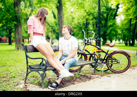 Young couple in a park, sitting on bench, Osijek, Croatia - Stock Photo
