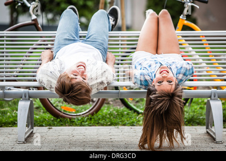 Young couple on a bench having fun, upside down, Osijek, Croatia - Stock Photo