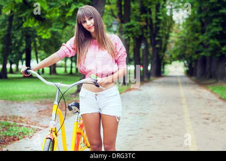 Young woman pushing bicycle in a park, Osijek, Croatia - Stock Photo