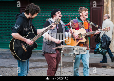 3 young adult men playing musical instruments in the streets of Lincoln - Stock Photo