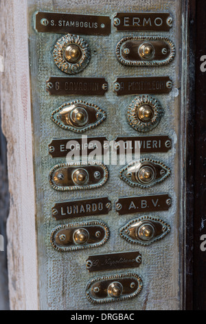 Brass Doorbell Buttons and Family Name Plates on an Entrance Panel to an Apartment Building, Venice, Italy - Stock Photo