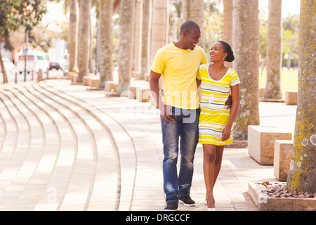 cheerful young afro American couple walking on urban street - Stock Photo