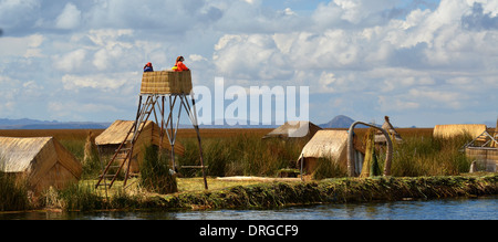 Uros Indian woman looking out from a watchtower on a reed island in Lake Titicaca August 3, 2013. - Stock Photo