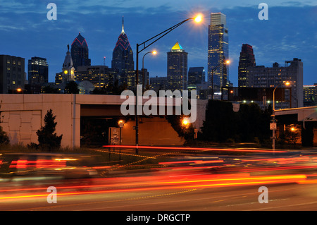 Philadelphia Skyline at dusk with Interstate 676 in the foreground. Downtown Philadelphia buildings in the background. - Stock Photo