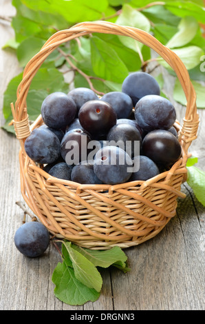 Plums in basket on the wooden table - Stock Photo