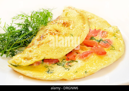 Omelet with tomatoes and herbs on white plate - Stock Photo