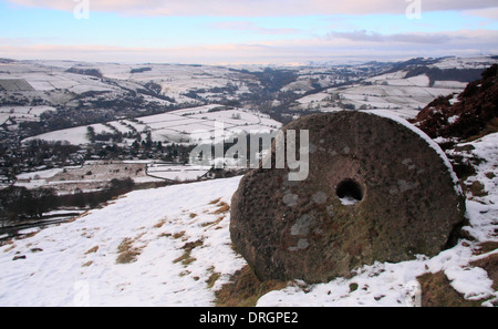 Snowfall over abandoned  millstone on Curbar Edge looking across the Derwent Valley over Calver, Peak District NP - Stock Photo