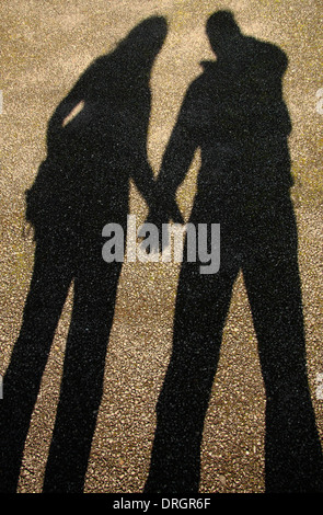 A couple cast ashadow whilst holding hands, England, UK - Stock Photo