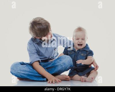 Großer Bruder mit kleiner, weinender Schwester - siblings - Stock Photo