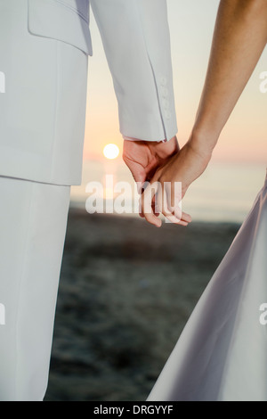 Händchenhalten am Strand bei Sonnenaufgang - holding hands at sunrise at the beach - Stock Photo