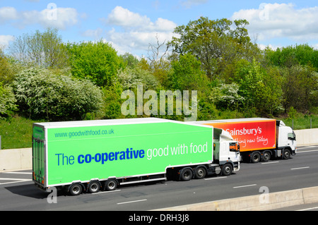 Co op food supply chain store delivery hgv truck &trailer overtaking Sainsburys supermarket food delivery lorry - Stock Photo