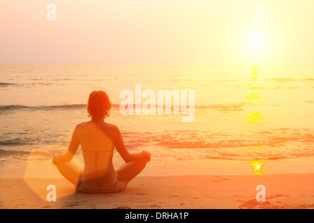 Young girl practicing yoga on the beach - Stock Photo