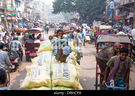 Porter resting on sacks of spices in the spice market, Old Delhi India - Stock Photo