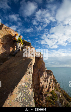 Walker climbing a flight of stone steps on the Bog of Frogs Loop, Red Rock, Howth Coastal Path, County Dublin, Ireland. - Stock Photo