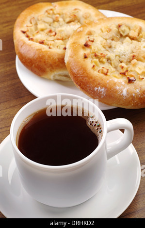 Cup of coffee and round bun with apple on table - Stock Photo